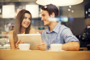 Flirting couple in cafe using digital tablet